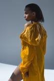 Young african american woman in wet yellow raincoat posing in studio Stock Image
