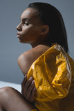 Young african american woman in wet yellow raincoat posing in studio. Sensual young african american woman in wet yellow raincoat posing in studio Stock Photos