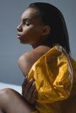 Young african american woman in wet yellow raincoat posing in studio Stock Photos
