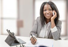 Young african american woman writing, and giving a call with mob Stock Photos
