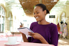 Young african american woman writing notes at cafe Stock Images