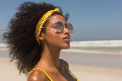 Young African American woman in yellow bikini and sunglasses standing on the beach royalty free stock image