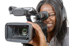 Young African American women with professional video camera. A young African American woman with professional video camera and headphone Royalty Free Stock Image