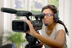 Young African American women with professional video camera. A young African American woman with professional video camera and headphone Royalty Free Stock Photos