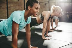 Smiling young woman doing pushups with friends at the gym