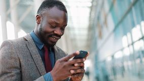 Young African Americanman using app on smartphone in city near the office center Handsome young businessman using. Smartphone smiling happy. The concept of stock video
