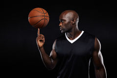 Young african athlete balancing basketball on his finger. Portrait of young african athlete balancing basketball on his finger against black background. Focused Stock Photo
