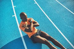 Young African athlete doing crunches on a running track royalty free stock images