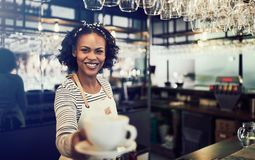 Young African barista offering up a fresh cup of coffee. Young African barista standing behind the counter of a trendy cafe holding up a fresh cup of coffee royalty free stock photography