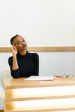 Young African or black American woman holding hand near face thinking and looking away at desk in office Stock Image