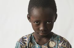 Young African boy showing his angry face, isolated on white. Beautiful shot of African children taken in a studio in Bamako, Mali Stock Photography