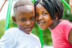 Young African brother and sister joining heads outdoors. royalty free stock images