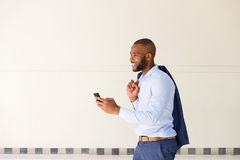 Young african business man walking outdoors with mobile phone Royalty Free Stock Images