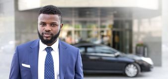 Young african businessman standing near the office building and looking at camera stock photos