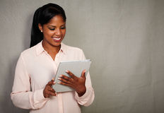 Young african businesswoman holding a tablet. Against grey texture background - copy space Royalty Free Stock Photography
