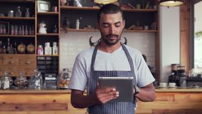Male owner at his coffee shop using digital tablet