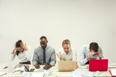 Young men and women sitting at office and working on laptops. Emotions concept royalty free stock photos