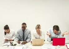 Young men and women sitting at office and working on laptops. Emotions concept stock photos