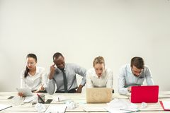 Young men and women sitting at office and working on laptops. Emotions concept stock images