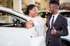 Visiting car dealership. couple holding key of their new car, looking at camera. Young african couple with car keys on car showroom background Royalty Free Stock Photos
