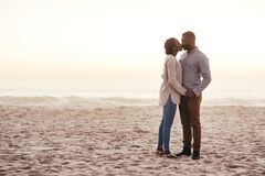 Romantic young African couple kissing on a beach at dusk stock images