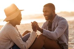 Young African couple sitting together on a beach at sunset. Smiling young African couple sitting and holding hands together on a sandy beach while enjoying a Royalty Free Stock Images