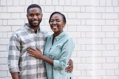 Young African couple smiling while standing together in the city. Smiling young African couple hugging while standing together in front of a brick wall in the royalty free stock photography