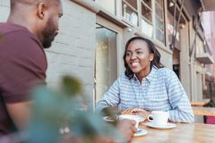 Young African couple talking together at a sidewalk cafe table. Smiling young African couple sitting together at a table drinking coffee and having a stock photo