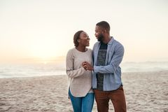 Young African couple walking on a beach at sunset laughing. Content young African couple laughing and talking while walking hand in hand together down a sandy stock photo