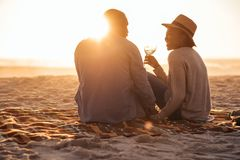 Young African couple watching a beach sunset and drinking wine. Romantic young African couple sitting together on a sandy beach at dusk toasting each other with royalty free stock photo