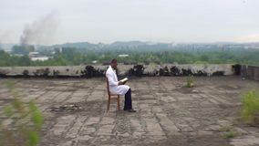 The young african doctor is sitting on the roof of the ruined hospital and reading the book at the background of the. Beautiful landscape stock video