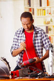 Young African Ecuadorian male Technician pucker his face while he is fixing a wood sander with a screwdriver.  Stock Photo