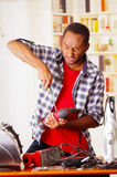 Young African Ecuadorian male Technician pucker his face while he is fixing a wood sander with a screwdriver.  Royalty Free Stock Image