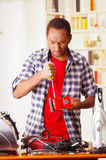 Young African Ecuadorian male Technician pucker his face having problems while he is fixing a red sander with a. Screwdriver Stock Image