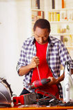 Young African Ecuadorian male Technician pucker his face having problems while he is fixing a red wood sander with a. Screwdriver Stock Images