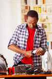 Young African Ecuadorian male Technician pucker his face while he is repairing a machine.  Royalty Free Stock Photo