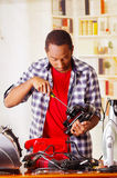 Young African Ecuadorian male Technician repairing a toaster with a screwdriver.  Stock Photos