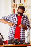 Young African Ecuadorian male Technician wearing protection glasses and using a metal cutter with office background.  Stock Photography