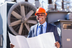 Young african electrical manager holding blueprint. Cheerful young african electrical manager holding blueprint in electric substation Stock Photo