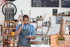Young African entrepreneur hard at work in his trendy cafe stock photography