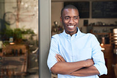 Young African entrepreneur leaning on the door to his cafe. Handsome young African entrepreneur smiling confidently while standing with his arms crossed at the royalty free stock photo