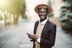 Young Afro american entrepreneur smiling at his phone in a city street royalty free stock photos