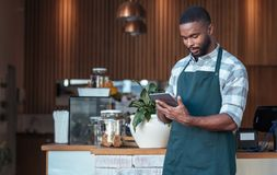 Young African entrepreneur standing in his cafe using a tablet Royalty Free Stock Image