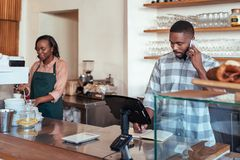 Young African entrepreneurs working together behind their cafe counter. Young african entrepreneur talking on a cellphone and writing in a notebook while royalty free stock photography