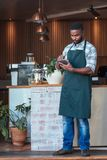 Young African entrepreneur working with a tablet in his cafe. Young African entrepreneur in an apron standing at the counter of his trendy cafe using a digital Stock Photography