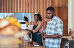 Young African entrepreneurs working together behind their cafe counter Royalty Free Stock Photography