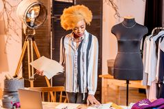 Fashion designer working at the office. Young african fashion designer working with clothes drawings and laptop sitting at the studio interior with different stock images