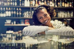 Smiling African entrepreneur leaning on the counter of her cafe. Young African female entrepreneur smiling confidently while leaning on the counter of her trendy stock images