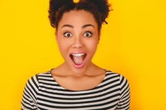 Young african woman isolated on yellow wall studio teen style shouting close-up. Young african female teenager isolated on yellow wall shouting excited looking Royalty Free Stock Image