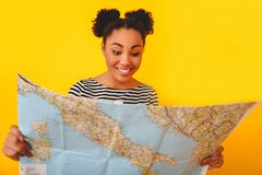 Young african woman isolated on yellow wall studio teen style traveler choosing destination. Young african female tourist teenager isolated on yellow wall Royalty Free Stock Photography